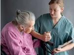 Una enfermera ayudándo a caminar a una envejeciente