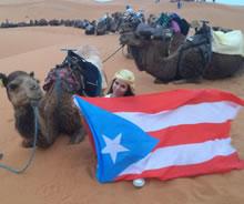 Deisimariely sentada en el piso al lado de un camello con la bandera de Puerto Rico