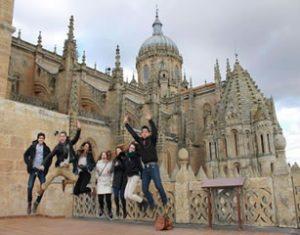 Grupo de jóvenes posando frente a un edificio parecido a un castillo