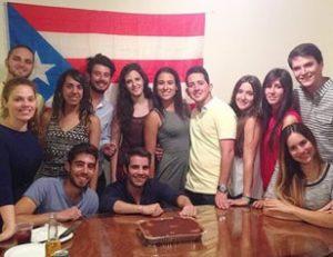 Grupo de jóvenes posando con la badera de Puerto Rico en fondo