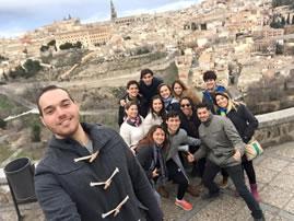 Giovanni con un grupo de amigos posando frente a una ciudad