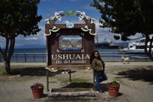 Jenilee posando al lado de un letrero que dice: Ushuala fin del mundo