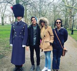 Tres jóvenes posando junto a un guardia