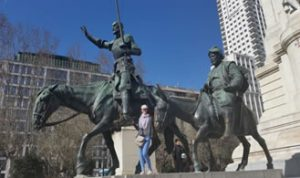 Maryse parada frente a un escultura de Don Quijote y Sancho Panza montados a caballo