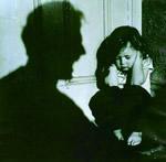Un niño agachado en un esquina tapándose los oídos y la sombra de un hombre gritándole