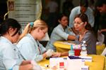 Estudiantes de enfermería realizando unas pruebas de sangre a una profesora en una feria de salud