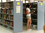 Estudiante ojeando un libro en los anaqueles de la Bibliotecca