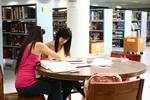 Estudiantes haciendo tarea sentadas en una mesa de la Biblioteca